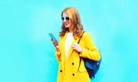 Fashion beautiful smiling woman using smartphone. On colorful blue background stock images
