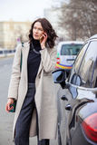 Fashion. beautiful woman in a bright coat talking on the mobile Stock Photography