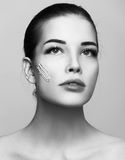 Fashion beautiful woman with cream on another cheek Stock Image