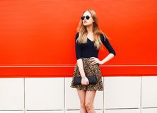 Fashion beautiful woman in leopard skirt sunglasses handbag clutch posing over colorful red Stock Photography