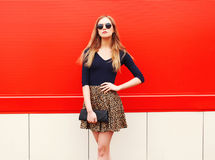Fashion beautiful woman in leopard skirt sunglasses handbag clutch posing over red colorful Stock Images