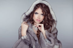 Fashion beautiful woman posing in fur coat. Winter Girl  Model i. N Luxury clothes and snowy furry hood Isolated on gray background Stock Image