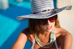 Fashion beautiful woman relaxing at poolside on summer vacation Royalty Free Stock Image