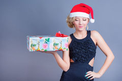 Fashion beautiful woman in a santa hat with presen Royalty Free Stock Photos