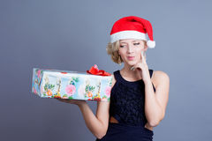 Fashion beautiful woman in a santa hat with presen Royalty Free Stock Images