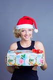 Fashion beautiful woman in a santa hat with presen Stock Images