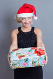 Fashion beautiful woman in a santa hat with presen Stock Image