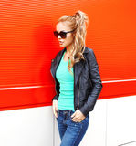 Fashion beautiful woman in sunglasses black rock jacket walking at city over red. Background Royalty Free Stock Photos