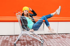 Fashion beautiful woman in trolley cart wearing black jacket hat over colorful orange Stock Photo