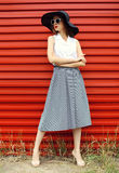 Fashion beautiful woman wearing a black straw hat, sunglasses and striped skirt over red Stock Photos