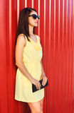 Fashion beautiful woman wearing a yellow dress and sunglasses with handbag clutch Royalty Free Stock Photography