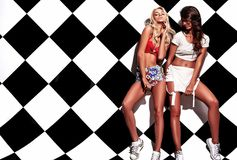 Brunette and blond models in rnb style clothes posing near chess wall Stock Photo