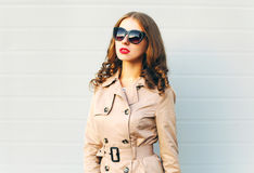 Fashion beautiful young woman wearing a black sunglasses and coat over grey Stock Image