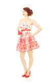 Fashion beauty 50s style. Red headed beautiful woman styled in 1950s floral print dress and makeup. High key image on a white background stock photo