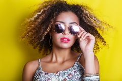 Fashion Beauty afro american Model Girl with sunglasses on yellow background. Fashion Beauty afro american Model Girl with sunglasses royalty free stock photo