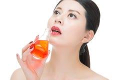 Fashion beauty asian woman drinking chemistry makeup cosmetic li Royalty Free Stock Image