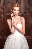 Fashion beauty bridal shooting. Beautiful fashion bride in wedding dress posing in front of woody background. Royalty Free Stock Photo