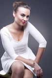 Fashion and Beauty Concepts. Portrait of Stylish Glamorous Caucasian Woman in White Dress Against Gray Royalty Free Stock Photos