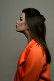 Fashion beauty female brunette with red lips and orange jacket Stock Image