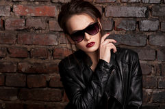 Fashion beauty girl in black leather jacket and sunglasses Royalty Free Stock Photo