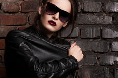 Fashion beauty girl in black leather jacket and sunglasses Stock Photos
