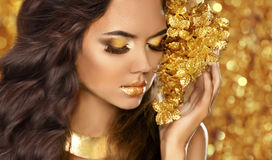 Fashion Beauty Girl Portrait. Eyes makeup. Golden jewelry. Attractive woman model with long brown hair over bokeh lights glitter. Background stock photography