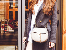 Fashion and Beauty. A handbag and a gray coat on the girl. Close-up, street-style. Royalty Free Stock Photography