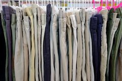 A row of many men`s pants hanging on a clothes rank and selling in a shop royalty free stock photos