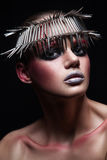Fashion beauty model with metallic headwear and shiny silver red makeup and blue eyes and red eyebrows on black background Stock Images