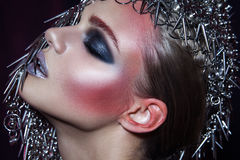 Fashion beauty model with metallic headwear and shiny silver red makeup and blue eyes and red eyebrows on black background royalty free stock image