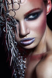 Fashion beauty model with metallic headwear and shiny silver red makeup and blue eyes and red eyebrows on black background Stock Photo