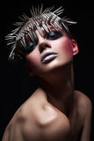 Fashion beauty model with metallic headwear and shiny silver red makeup and blue eyes and red eyebrows on black background.  stock photo