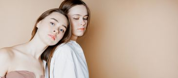 Fashion beauty models two sisters twins beautiful nude girls isolated on beige background, banner stock photography