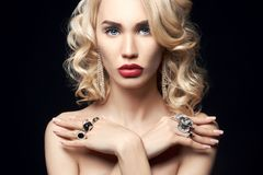 Fashion beauty Nude blonde woman on a dark background. Girl with. Jewels on the arms and neck. Skin care and beautiful makeup perfect girls. Luxury woman with Royalty Free Stock Images