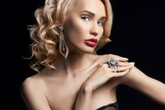 Fashion beauty Nude blonde woman on a dark background. Girl with. Jewels on the arms and neck. Skin care and beautiful makeup perfect girls. Luxury woman with Royalty Free Stock Photos