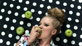 Fashion beauty portrait of blonde beautiful model biting an apple. Pin up style. stock video footage
