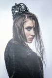 Fashion beauty portrait of young beautiful young woman with makeup and freckles on her face with black crown on her head Stock Image