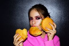Fashion, beauty.Sexy woman with perfect makeup eating hamburgers. Female beauty visage concept. royalty free stock photo