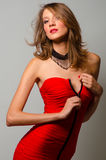 Fashion beauty unzipping red dress Stock Images