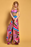 Fashion beauty woman in bright clothes.Expressive. Fashion beauty model in stylish bright clothes. Blonde woman in colorful luxury summer dress, glamor shoes stock photography