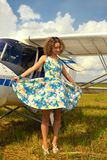 Fashion beautyful woman in pinup style dress nearby ultralight plane Stock Image