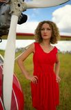 Fashion beautyful woman in red dress nearby ultralight plane Royalty Free Stock Images