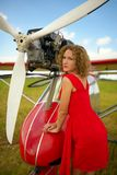 Fashion beautyful woman in red dress nearby ultralight plane Royalty Free Stock Image