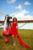 Fashion beautyful woman in red dress nearby ultralight plane Stock Image