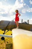 Fashion beautyful woman in red dress stays on a wing of the old plane Royalty Free Stock Photos