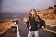 Fashion biker girl. Standing on the road with helmet in hands, traveling in overcast weather, active lifestyle concept Royalty Free Stock Image