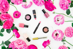 Fashion blogger desk with cosmetics, lipstick, eye shadows and pink roses and ranunculus on white background. Flat lay, top view. Royalty Free Stock Image