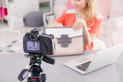 Fashion blogger filming video. Fashion blogger with woman`s bag and laptop filming her video Royalty Free Stock Photo