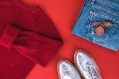 Woman fall/winter clothes laying on red background. Jeans, yellow knitted jumper, silver flat shoes. royalty free stock images