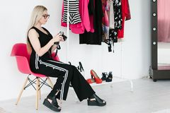 Fashion blogger review photo woman holding camera. Fashion blogger reviewing photos of trendy clothing. social media influencer at work. woman holding camera in stock photo